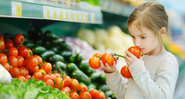 child in veggie section of grocery store